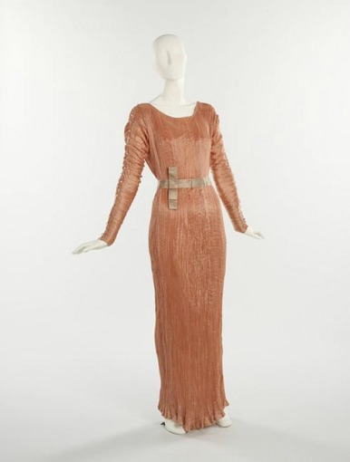 Fortuny, Mariano. Delphos dress, c1930. Peach pleated silk gown with Venetian clear glass beads. From the Collection Brooklyn Museum Costume Collection at the Metropolitan Museum of Art, Gift of the Brooklyn Museum, 2009.